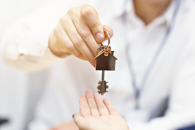 Sezione mediana dell'agente immobiliare e delle mani dell'acquirente con le chiavi in ufficio