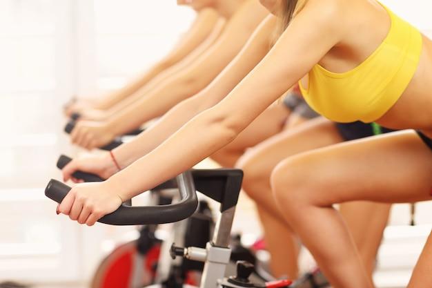 Sezione centrale del gruppo di donne sportive durante la lezione di spinning spinning