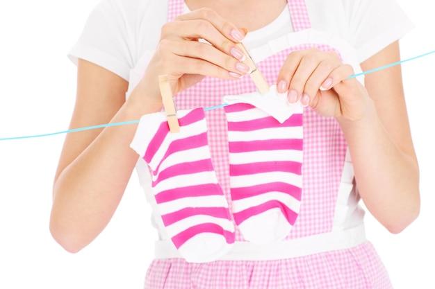 Una parte centrale di una donna che appende i calzini su sfondo bianco