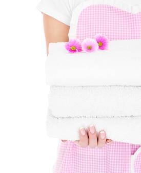 Una parte centrale di una donna che tiene un mucchio di asciugamani puliti e fiori