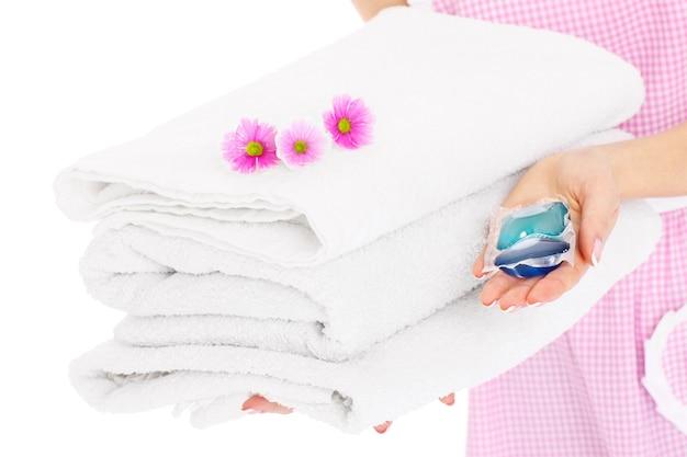 Una parte centrale di una donna che tiene in mano un mucchio di asciugamani puliti, compresse di gel e fiori