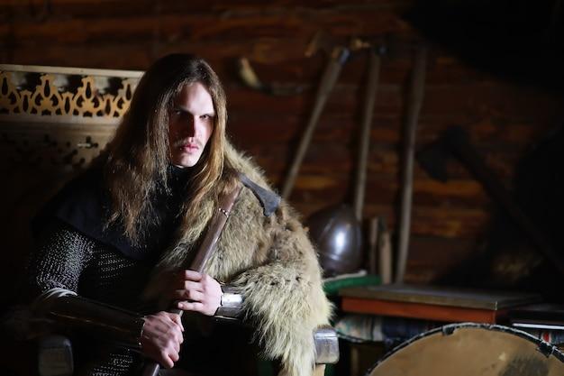 Un potente eroe con i capelli lunghi in armatura di cotta di maglia in un'antica sala. guerriero medievale nelle camere del cavaliere.