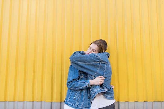 Possenti abbracci sullo sfondo della parete gialla. giovani coppie alla moda che abbracciano sul fondo vivace