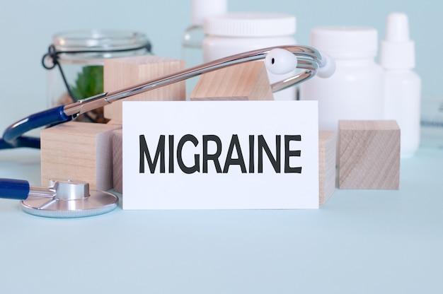 Parole di migraina scritte su tessera medica bianca, con stetoscopio, fiore verde, pillole mediche e blocchi di legno sulla parete blu. concetto medico e sanitario. messa a fuoco selettiva