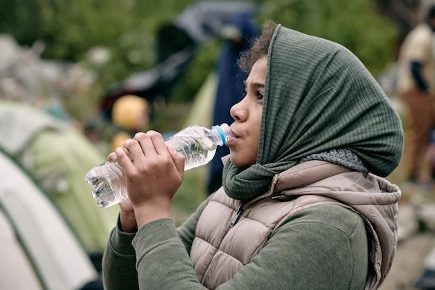 Ragazza migrante che beve acqua