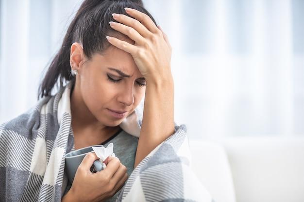 Migrene che ha una femmina tiene la testa dolorante in isolamento a casa.