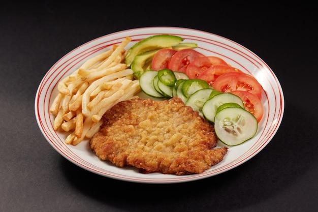 Milanesa de pollo con papas fritas y ensalada de pepino tomate y aguacate