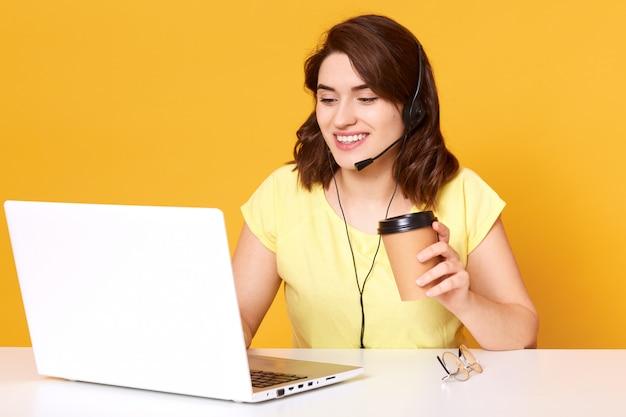 Operatore libero professionista che lavora online con cuffie e computer portatile in ufficio oa casa. la femmina allegra della call center che parla con il cliente e che beve il caffè, beind di buon umore.