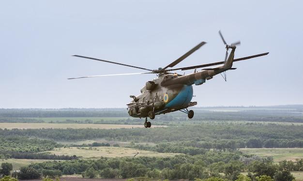 Elicottero militare che vola sopra i campi verdi
