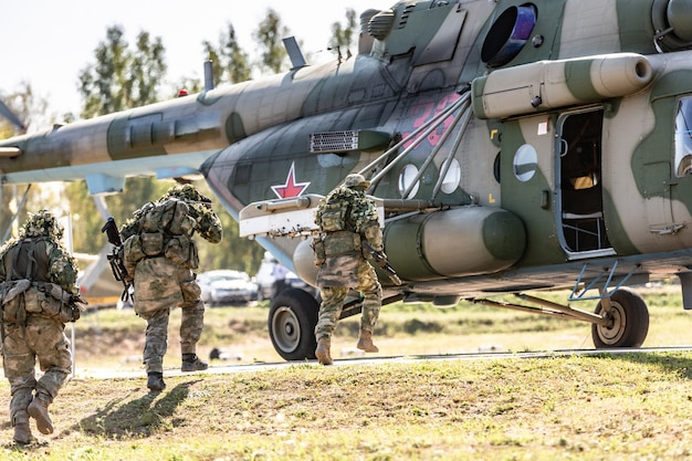 Elicottero militare in piedi a terra e soldati che vi caricano.
