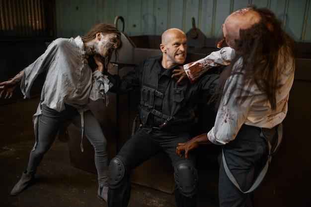 L'uomo militare combatte con gli zombie in una fabbrica abbandonata, luogo spaventoso. orrore in città, attacchi di striscianti raccapriccianti, apocalisse del giorno del giudizio, mostri malvagi sanguinanti