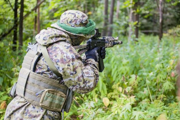 Uomo militare nella foresta con una mitragliatrice. formazione e istruzione dei soldati. l'uomo è pronto a sparare