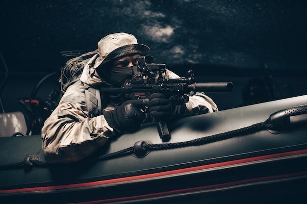 Un militare in pieno combattimento sta seguendo un bracconiere su una barca con un lampeggiatore.
