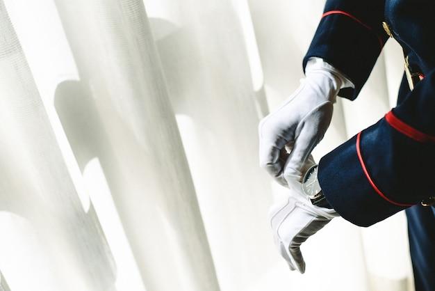 Le mani dell'uomo militare che indossano alcuni guanti bianchi eleganti.