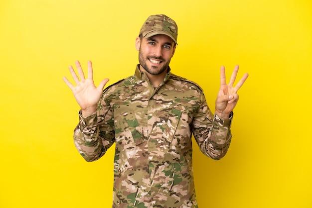 Militare isolato su sfondo giallo contando otto con le dita