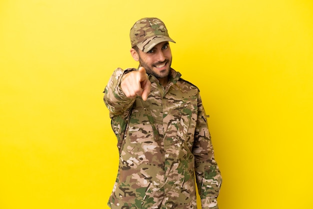 Il militare isolato su sfondo giallo ti punta il dito contro con un'espressione sicura
