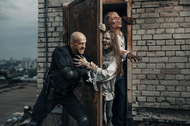 L'uomo militare non lascia che gli zombi sul tetto di un edificio, inseguano mortalmente. orrore in città, attacco di striscianti raccapriccianti, apocalisse