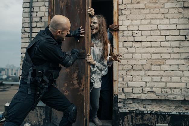 L'uomo militare non lascia che gli zombi salgano sul tetto