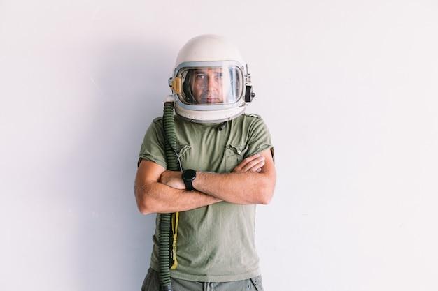 Militare con casco astronauta cosmonauta, braccia incrociate, su un muro bianco