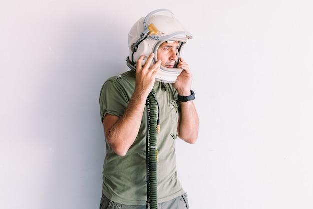 Militare con casco astronauta cosmonauta, su una parete bianca