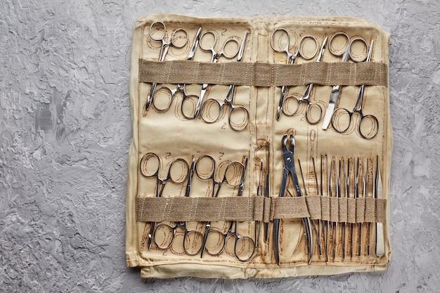 Kit chirurgico da campo medico militare. strumento di lavoro di un chirurgo di centrocampo che opera pinzette. chirurgia strumentale
