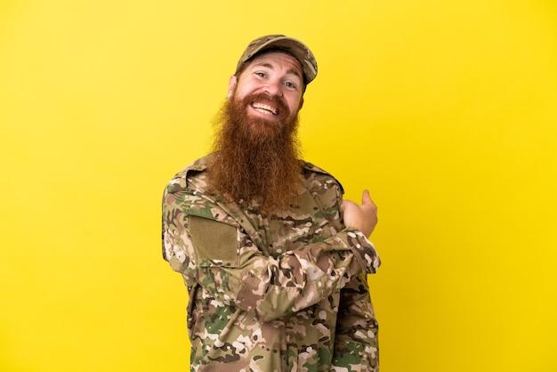Uomo rosso militare sopra isolato su sfondo giallo che punta indietro