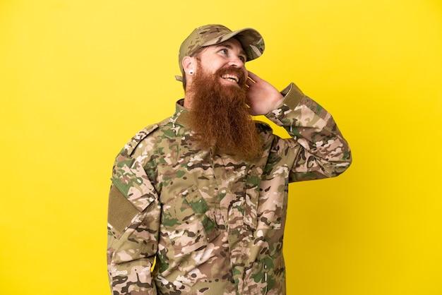 Uomo rosso militare sopra isolato su sfondo giallo pensando a un'idea