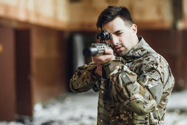 Un militare prende di mira e tiene un grosso fucile nell'edificio