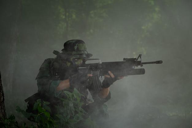 Thailandia militare: soldato thailandese tenendo la pistola in uniforme dell'esercito completo. rangers per trovare notizie