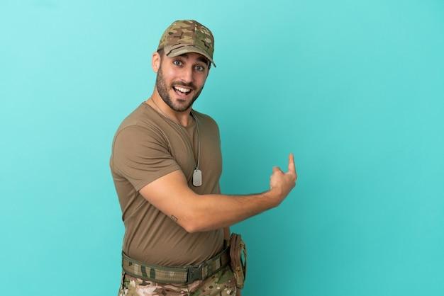 Militare con medaglietta sopra isolato su sfondo blu che punta indietro