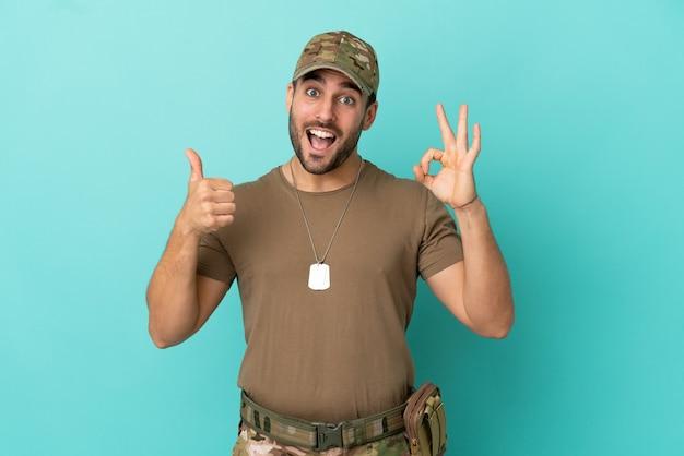 Militare con medaglietta sopra isolato su sfondo blu che mostra segno ok e gesto pollice in alto