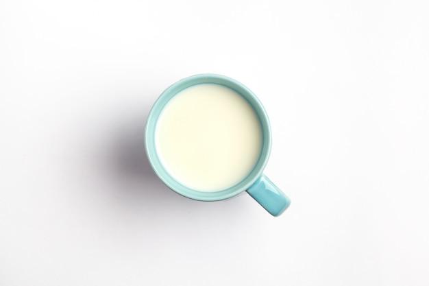 Latte in una tazza blu isolata su una superficie bianca, vista dall'alto.