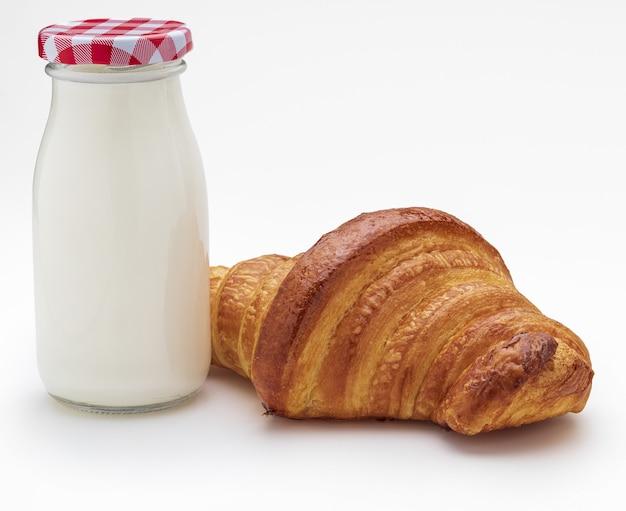 Bottiglia per il latte e croissant, copia dello spazio. isolato su sfondo bianco.