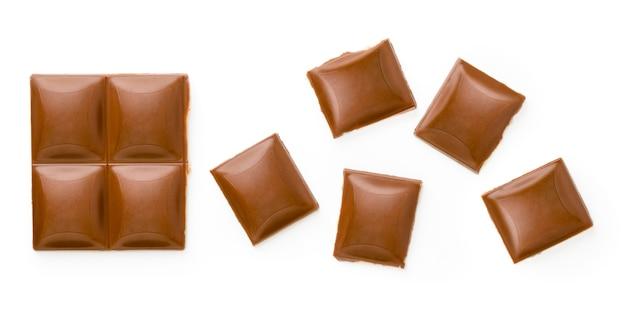 Vista superiore dei cubi rotti del cioccolato al latte isolata