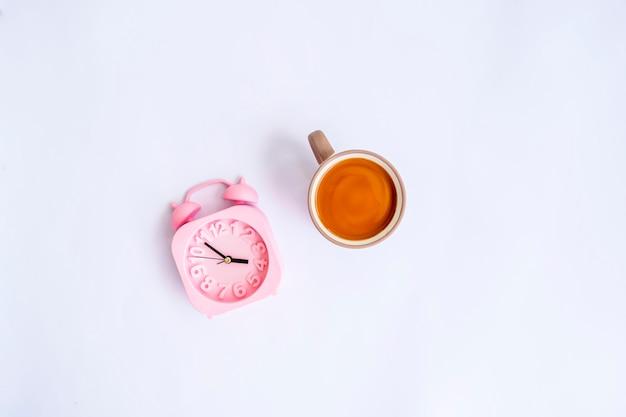 Caffè al latte e sveglia isolati su sfondo bianco, idea di concetto minimo.