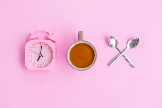 Caffè al latte, due cucchiai e sveglia isolati su sfondo rosa, idea concettuale minima.