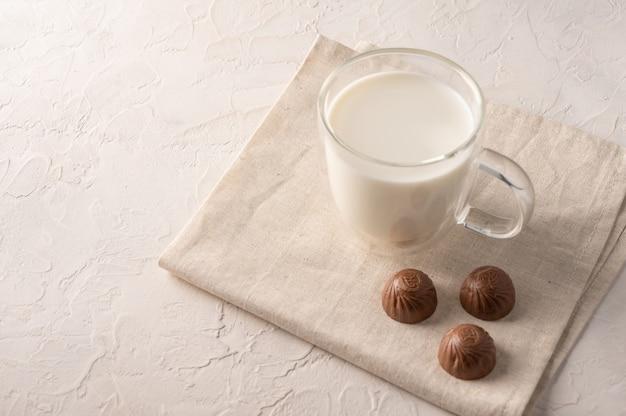 Latte in una tazza e cioccolatini su un tovagliolo di lino su sfondo chiaro.