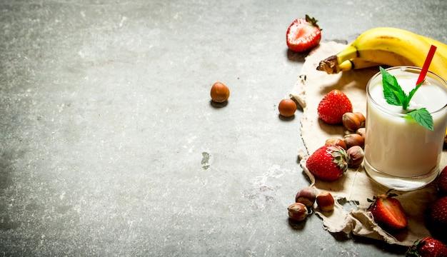Dessert al latte con noci, frutti di bosco e banane. sul tavolo di pietra.