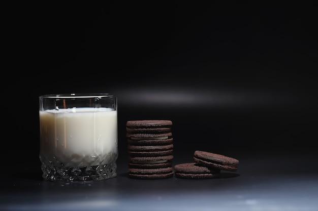 Bevanda al latte in un bicchiere. latte e biscotti della fattoria. deliziosa merenda con latte vaccino e pasticceria fresca.