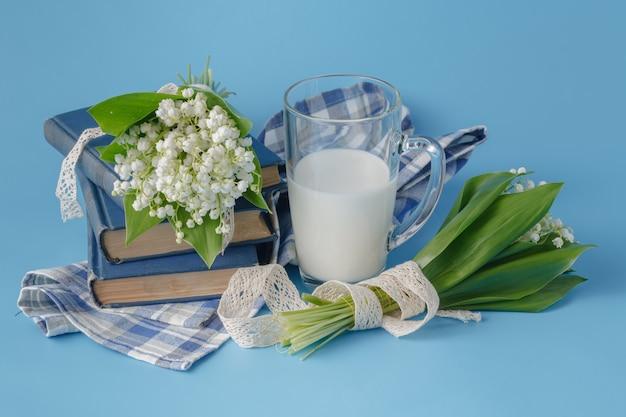Bicchiere di latte sul blu con fiori