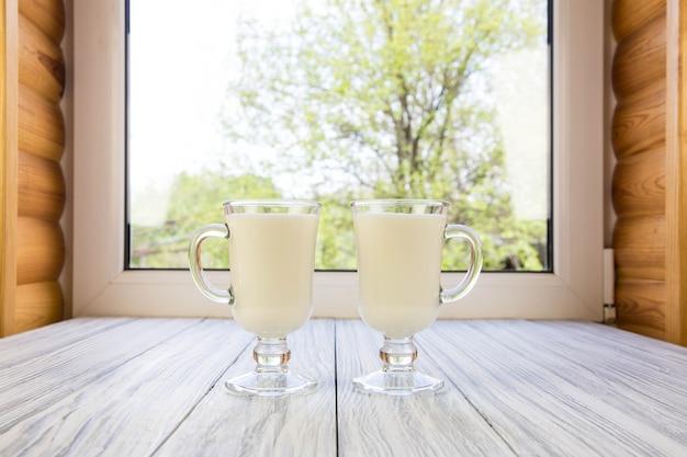 Latte in una tazza di vetro contro una finestra