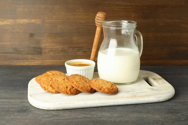 Biscotti al latte, miele e zucca sul tavolo di legno grigio.