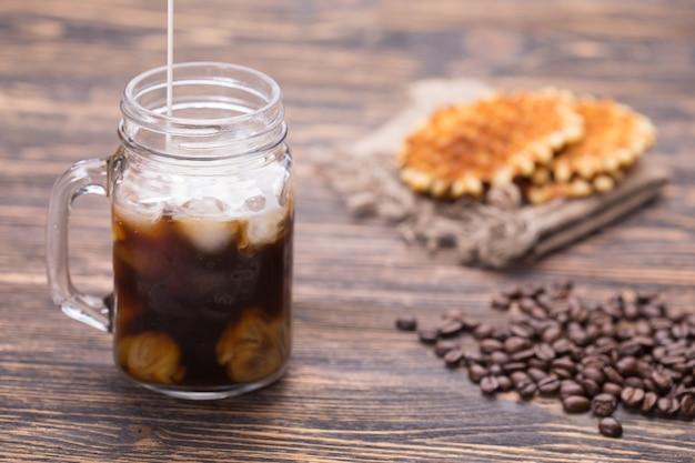 Il latte viene versato nel caffè. chicchi di caffè sullo sfondo