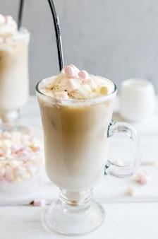 Il latte viene versato in un bicchiere con cubetti di ghiaccio di caffè, caffè freddo
