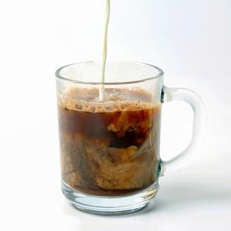 Latte versato in una tazza trasparente di caffè nero