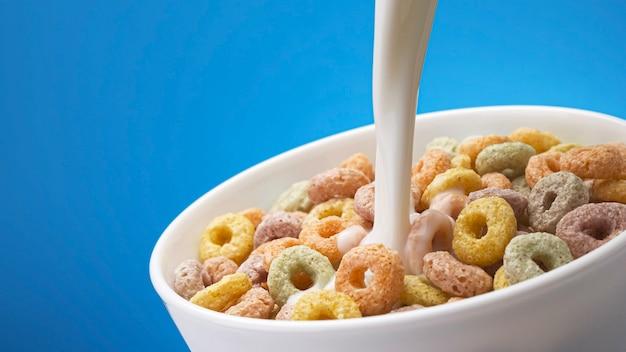 Versare il latte nella ciotola di anelli di mais colorati con schizzi, una sana colazione a base di cereali