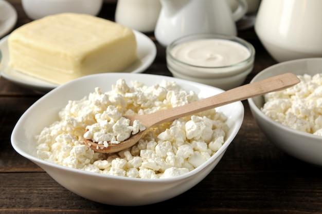 Latticini. primo piano della ricotta, latte, panna acida, formaggio, burro su una tavola di legno marrone.