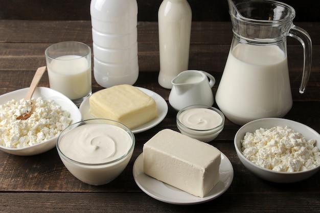 Latticini. latte, panna acida, formaggio, burro e ricotta su un tavolo di legno marrone