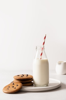 Latte per babbo natale in bottiglia e biscotti su bianco.