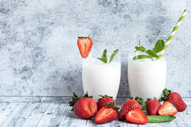Milk shake in due bicchieri e fragole fresche